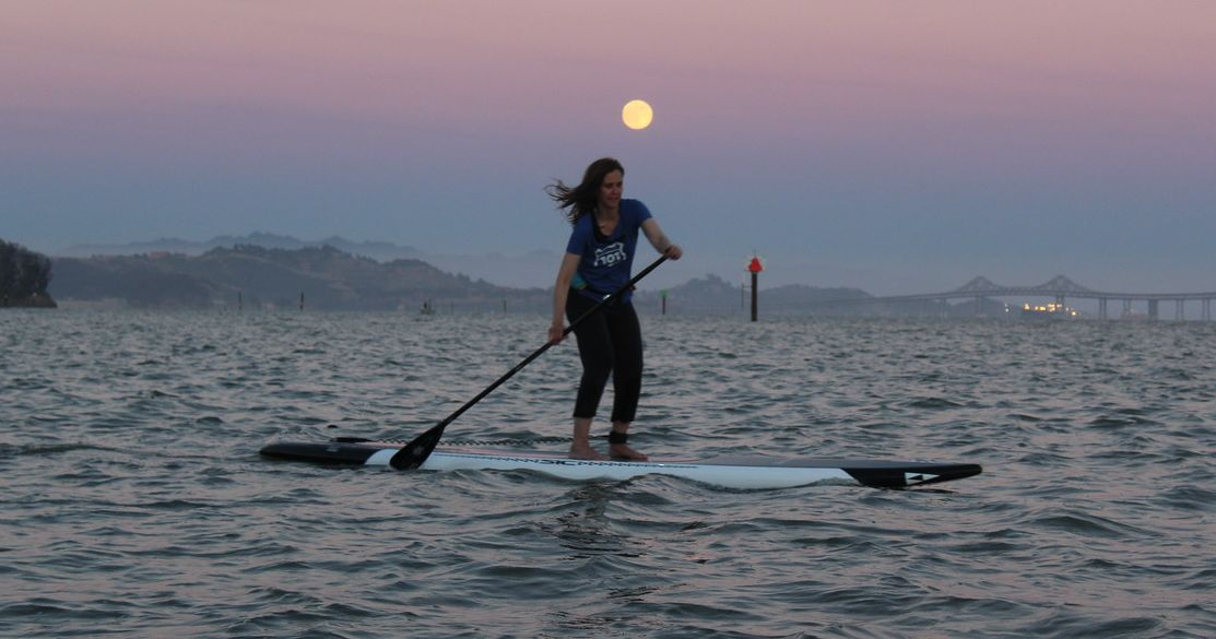 A Stand up paddleboarder glides under the moon on San Francisco Bay